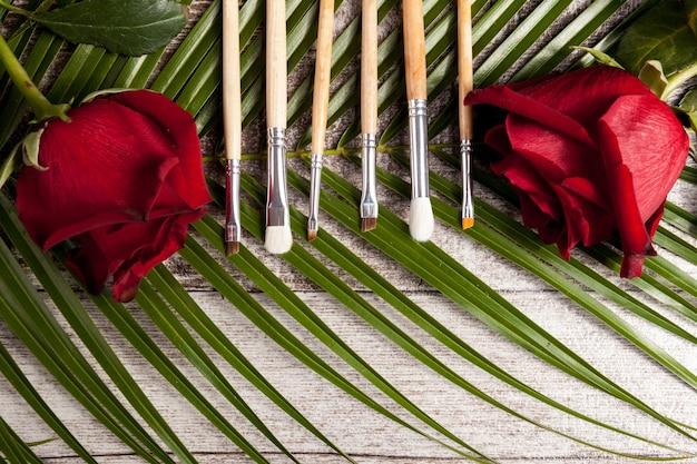 Schminkpinsel neben rosen auf holzuntergrund