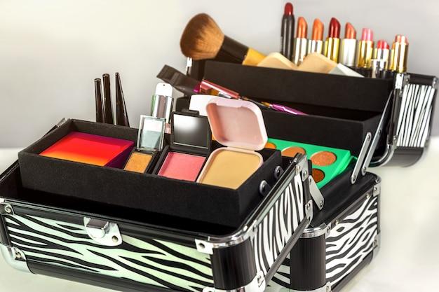 Schminktasche mit bunten lidschatten, lippenstiften, lipglosses, rouges und nagellacken