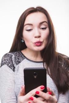 Schmollende lippen der frau beim machen des fotos mit mobiltelefon