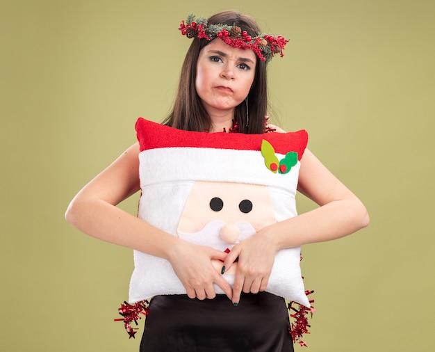 Schmollendes junges hübsches kaukasisches mädchen mit weihnachtskopfkranz und lametta-girlande um den hals, das ein weihnachtsmann-kissen hält und die kamera mit aufgedunsenen wangen einzeln auf olivgrünem hintergrund anschaut