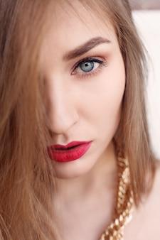 Schmuck, urlaub, luxus und menschenkonzept - schönes weibliches gesicht mit natürlicher perfekter haut. goldfrauenhaut. goldohrringe, ring und halskette. kosmetik, schönheit und maniküre auf den nägeln