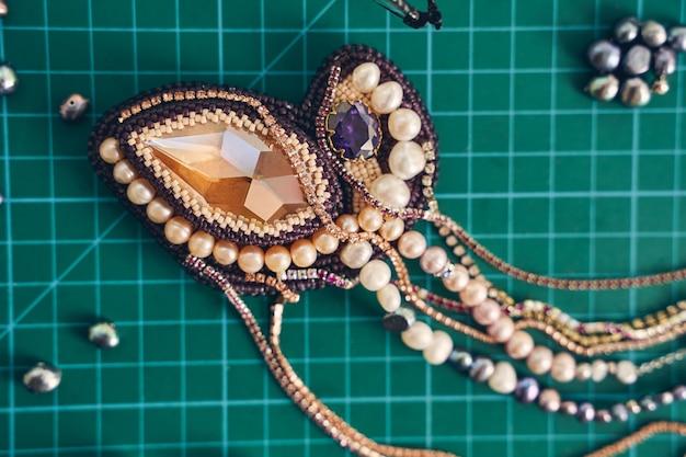 Schmuck vintage anhänger ornament aus goldfarbenen perlen und edelsteinen und perlen
