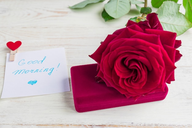 Schmuckgeschenkbox und bautiful rotrose auf hölzernem hintergrund. guten morgen auf weißem blatt papier wünschen