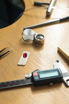 Schmuckhandwerk. juwelierpinzette, lupe, rubin-edelstein. die juwelier-graveur-werkzeuge auf dem hölzernen vintage-schreibtisch.