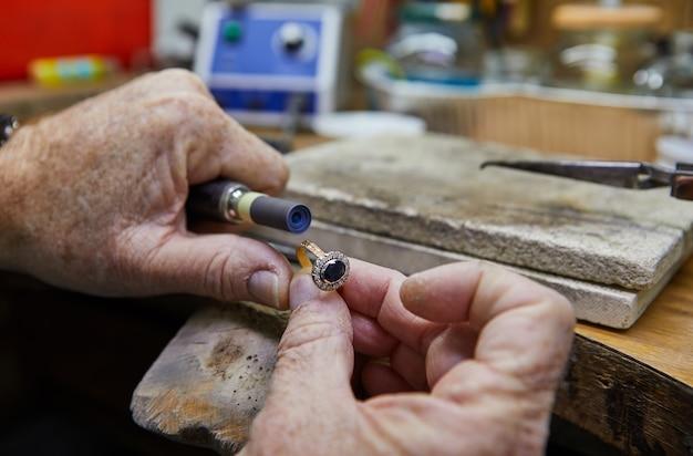 Schmuckherstellung. juwelier poliert einen goldring