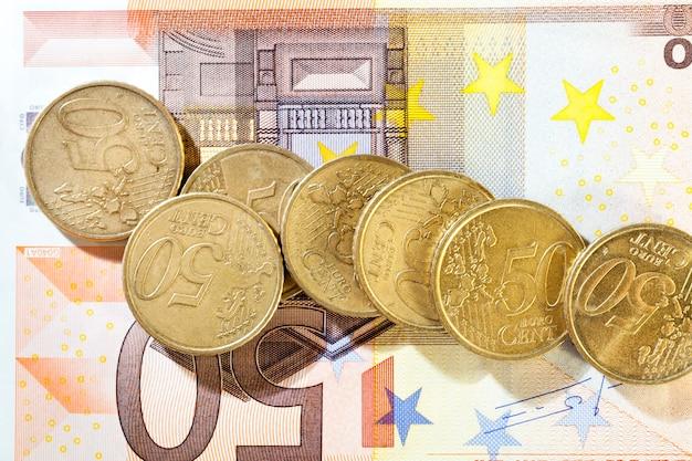 Schmutzige alte 50-cent-münzen und eine bargeldrechnung von 50 euro liegen zusammen, nahaufnahme