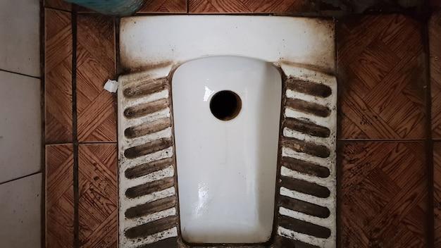 Schmutzige alte und staubige toilette in einem öffentlichen verlassenen gebäude. zerstörter hygieneraum.