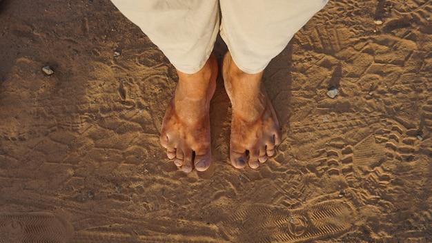 Schmutzige füße auf trockener erde