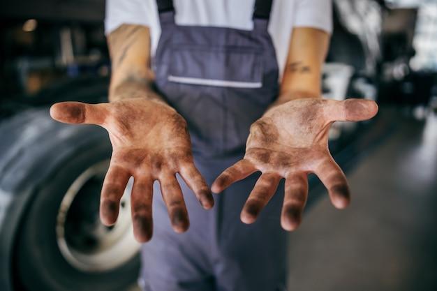 Schmutzige hände eines fleißigen mitarbeiters in overalls. manuelles jobkonzept.