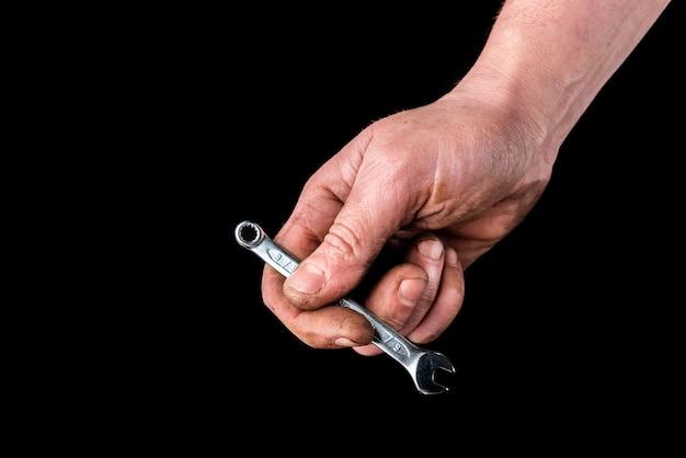 Schmutzige hand mit schraubenschlüssel auf schwarz.