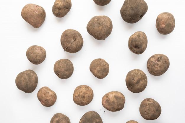 Schmutzige kartoffeln lokalisiert auf einem weißen hintergrund, draufsicht