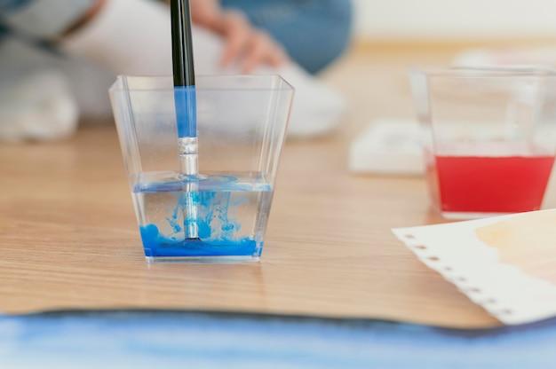 Schmutzige pinselfarbe aus blauem acryl im wasser