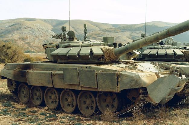 Schmutzige russische kampfpanzer am tankodrom in den bergen