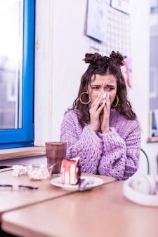Schmutzige serviette tragen. unangenehme frustrierte frau, die an grippe erkrankt ist und rotz ausbläst, während sie im café sitzt