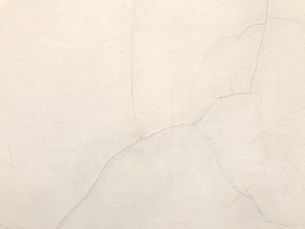 Schmutzige und gebrochene sahnefarbbetonmauer