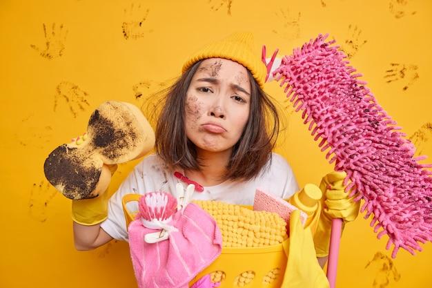 Schmutzige unzufriedene junge brünette asiatin sieht unglücklich aus, entfernt schmutz mit schwamm hält schmutzigen mopp in freizeitkleidung gekleidet, der damit beschäftigt ist, wäsche einzeln über gelber wand zu waschen?