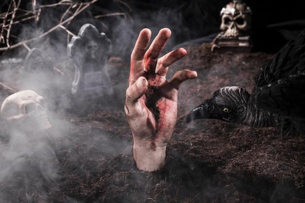 Schmutzige zombiehand und furchtsamer vogel am halloween-kirchhof