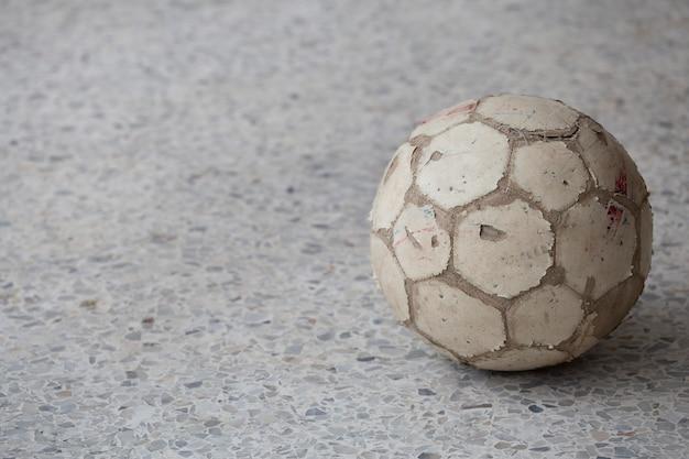 Schmutziger fußball auf boden.