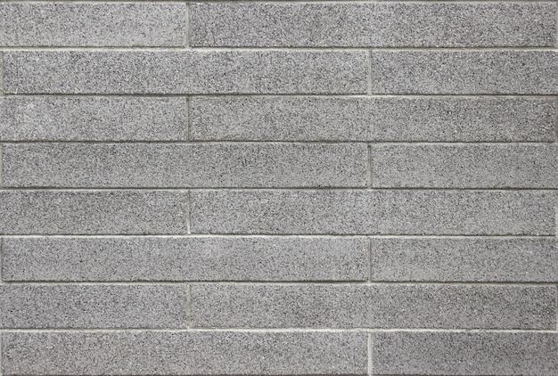 Schmutziger gealterter strukturierter innenarchitekturhintergrund der grauen ziegelsteinwand.