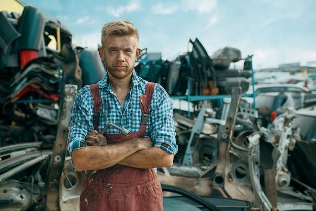 Schmutziger männlicher handwerker auf autoschrottplatz. autoschrott, fahrzeugschrott, automüll, verlassener, beschädigter und zerquetschter transport