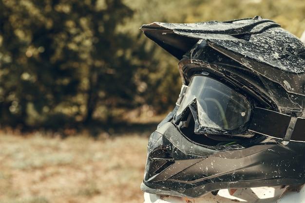 Schmutziger motorradmotocrosssturzhelm mit schutzbrillen