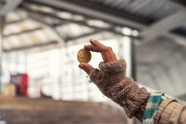 Schmutziger obdachloser, der goldmünze der kryptowährung hält