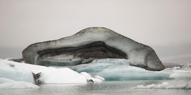 Schmutziger schmuddeliger schmelzender eisberg, der in wasser schwimmt