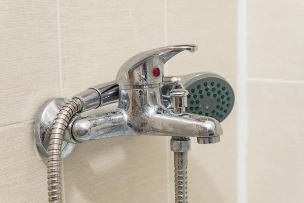 Schmutziger verkalkter duschmischerhahn, wasserhahn mit kalk darauf, nahaufnahmefoto