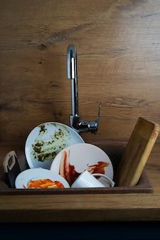 Schmutziges geschirr, schmutzige weiße teller in der küchenspüle. foto in hoher qualität