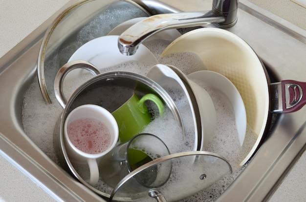 Schmutziges geschirr und ungewaschene küchengeräte füllten das spülbecken