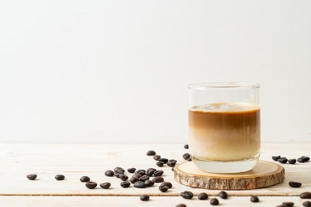 Schmutziges kaffeeglas, kalte milch, gekrönt mit heißem espresso-kaffee