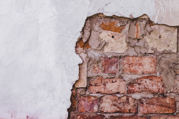 Schmutzweinlesebacksteinmauerbeschaffenheit und weißer stuckgebäudefassadenhintergrund
