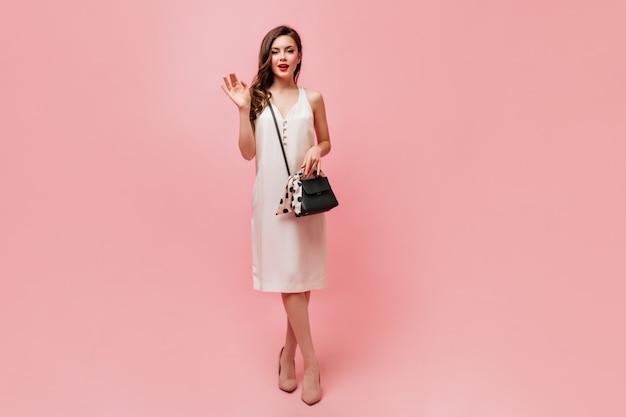 Schnappschuss der eleganten lockigen dame im weißen kleid mit schwarzer tasche. frau, die ihre hand über rosa hintergrund winkt.