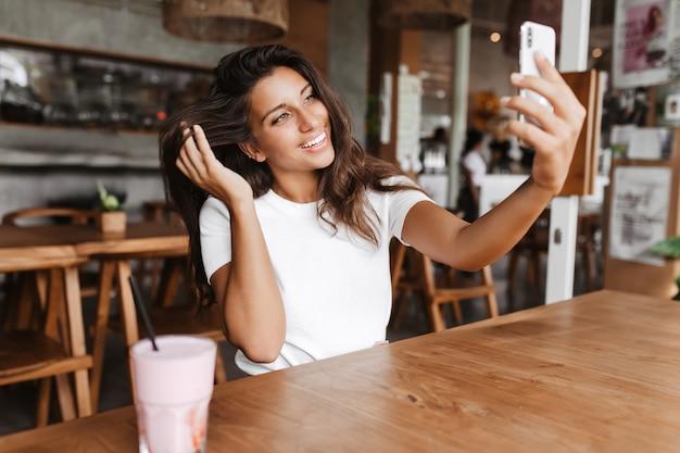 Schnappschuss der schönen gebräunten frau, die selfie im café nimmt