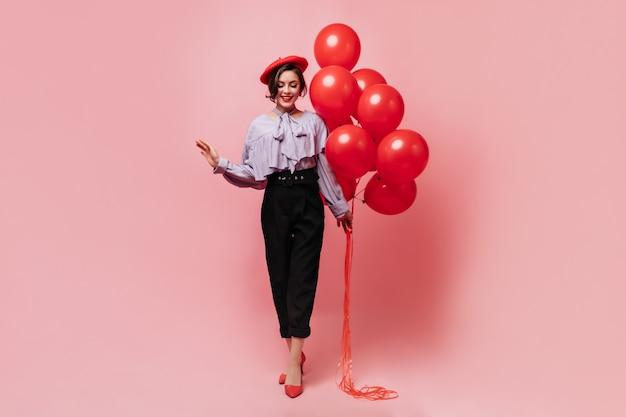 Schnappschuss eines jungen stilvollen mädchens, gekleidet in bluse, hose und baskenmütze. frau, die luftballons auf rosa hintergrund hält.