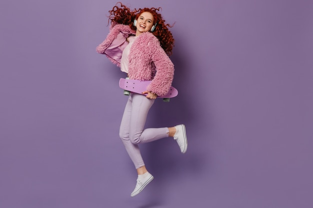 Schnappschuss im vollen wachstum des lustigen mädchens, das mit longboard springt. lockige frau, die in weißen jeans und im rosa mantel aufwirft.