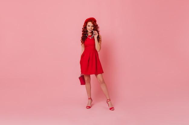 Schnappschuss in voller länge einer blauäugigen weiblichen ingwer-kokette in minimalistischem, hellem kleid, baskenmütze und mit roter tasche. frau, die hohe absätze trägt, brille beißt und rosa raum aufwirft.