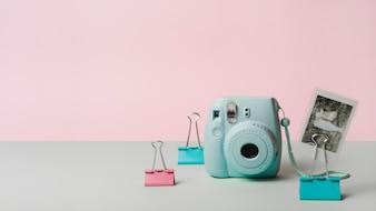 Schnappschussbild mit mini sofortiger Kamera- und Bulldoggebüroklammer gegen rosa Hintergrund