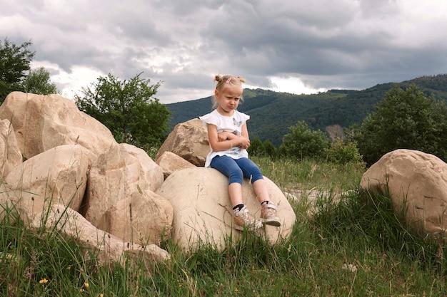 Schnarchendes mädchen, das auf einem großen stein auf einem hintergrund der berge sitzt
