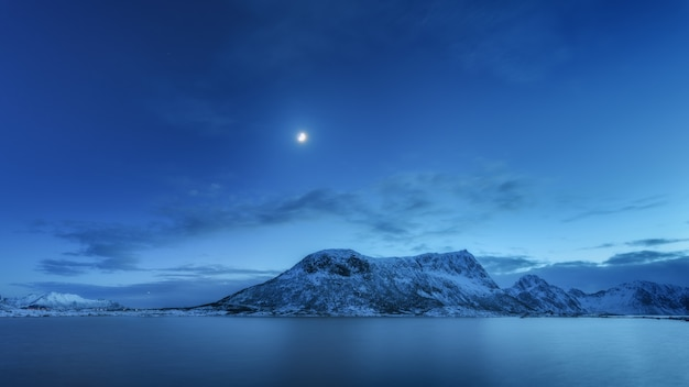 Schnee bedeckte berge gegen blauen himmel mit wolken und mond im winter in der nacht