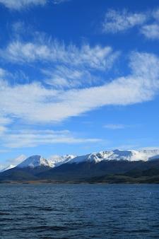 Schnee bedeckte gebirgszugansicht vom kreuzschiff auf spürhundkanal, ushuaia, argentinien mit einer kappe