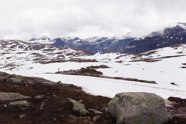 Schnee liegt vor blauen felsen summints in norwegen