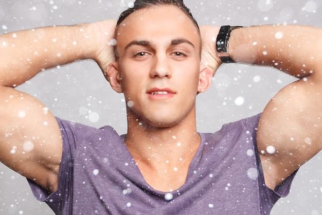 Schnee-, winter-, weihnachts-, emotions-, werbungs- und leutekonzept - hübscher junger mann über schneehintergrund, der kamera betrachtet. porträt des lachenden jungen mannes in den taschen, die gegen graue wand gelehnt sind.