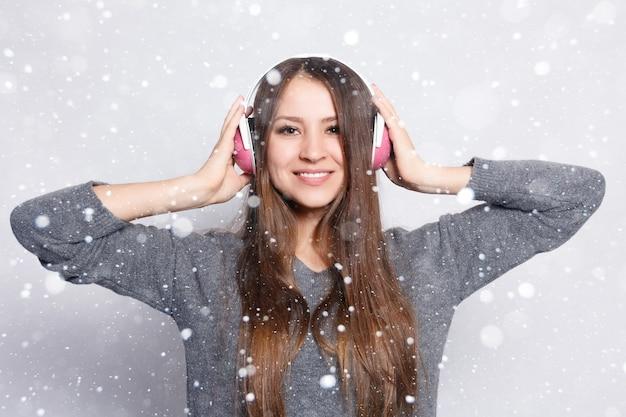 Schnee-, winter-, weihnachts-, menschen-, freizeit- und technologiekonzept - glückliche frau oder teenager-mädchen in kopfhörern, die musik vom smartphone hören und über schneehintergrund tanzen