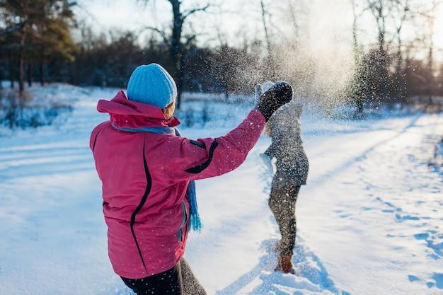 Schneebälle, die im winterwald spielen. familienmutter und -tochter, die den spaß draußen wirft schnee hat