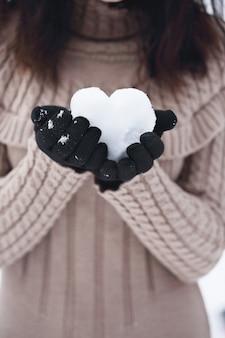 Schneeball in form eines herzens in den händen