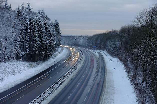Schneebedeckte autobahn in der abenddämmerung in deutschland