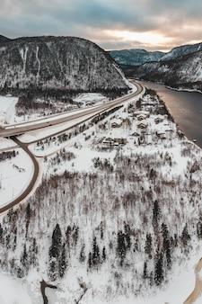 Schneebedeckte bäume und gebäude in der nähe von bergen