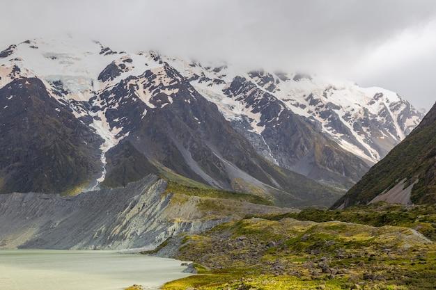Schneebedeckte berge über dem wasser lake muller south island new zealand