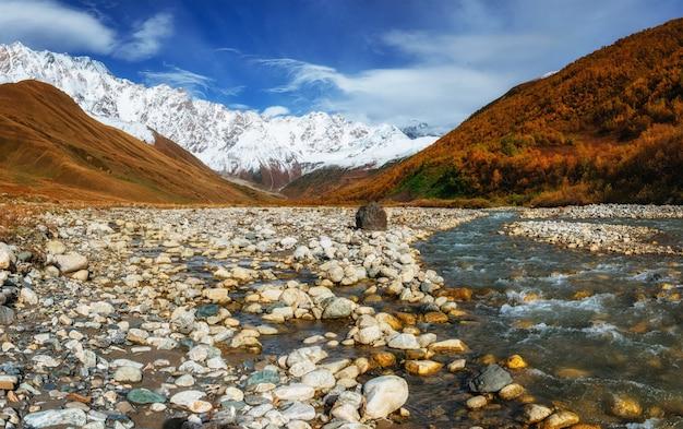 Schneebedeckte berge und lauter gebirgsfluss
